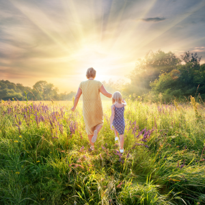 A woman and child walking through a meadow towards a brilliant sun.