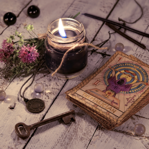 Oracle cards, a key, a candle, beads, a necklace, flowers